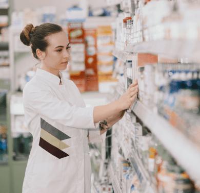 medicine-pharmaceutics-health-care-people-concept-female-pharmacist-taking-medications-from-shelf-min