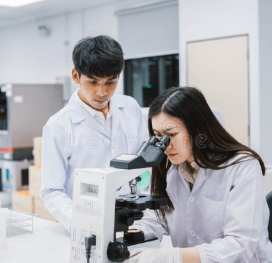 two-medical-scientist-working-laboratory-young-female-looking-microscope-select-focus-188779054-min